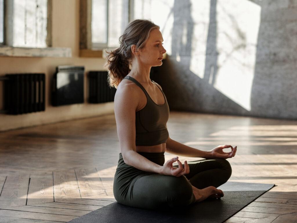 Yogalehrerin beim Meditieren und Eröffnen ihrer Stunde