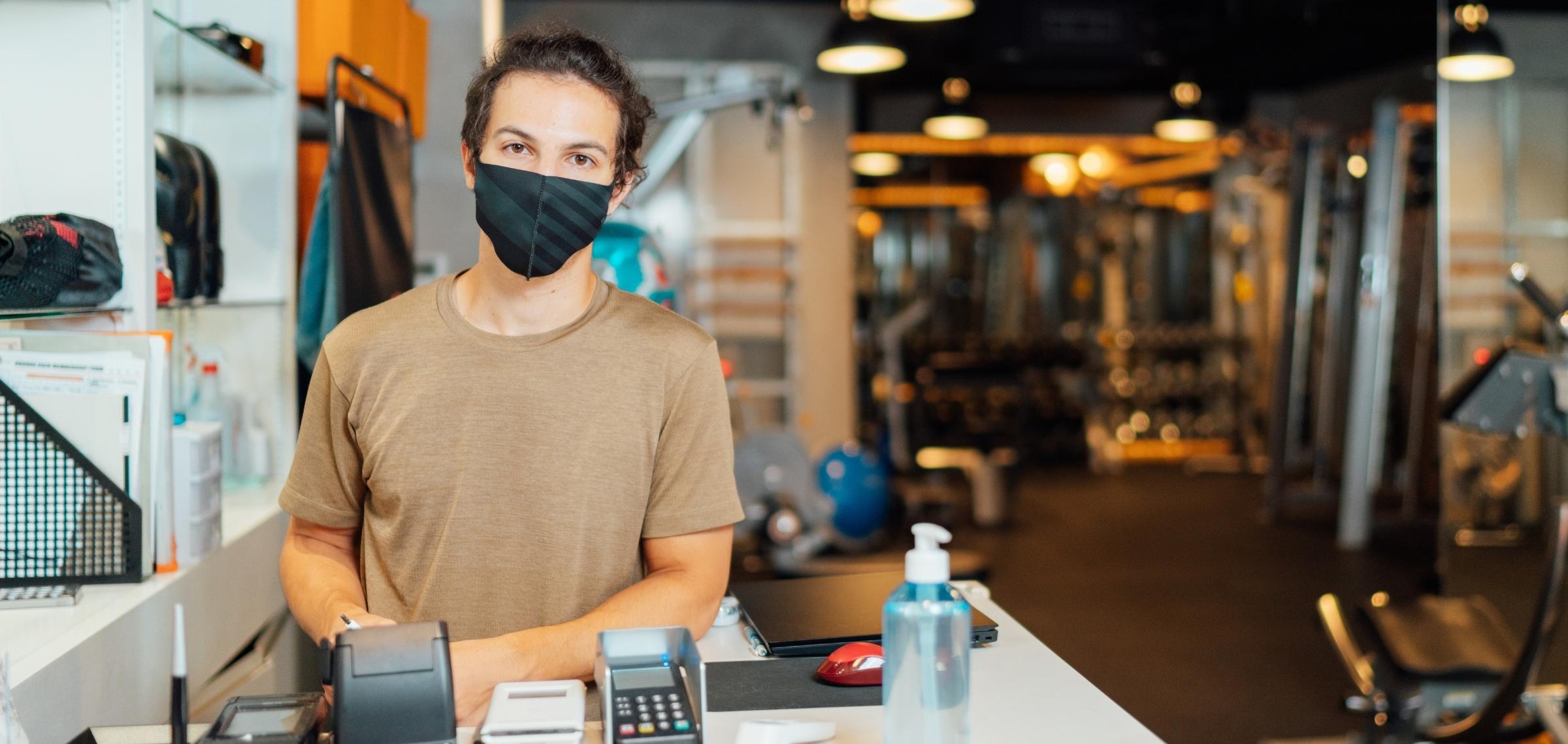 Mann mit Maske hinter Check-In-Schalter eines Studios - TSE Kasse für Studios und Sportstätten