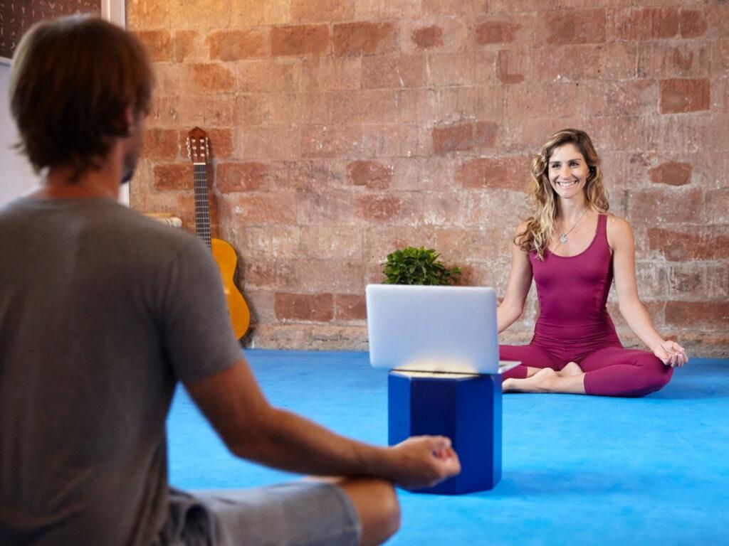 Yogalehrerin gibt eine hybride Klasse in ihrem Studio, nachdem sie ihr Studio wieder öffnen durfte