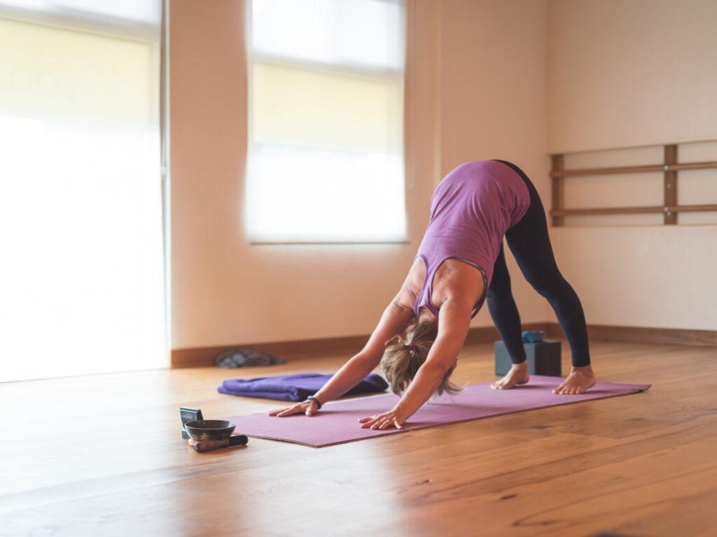 Frau macht Yoga im Studio nachdem sie ihr Yoga Studio wieder öffnen durfte