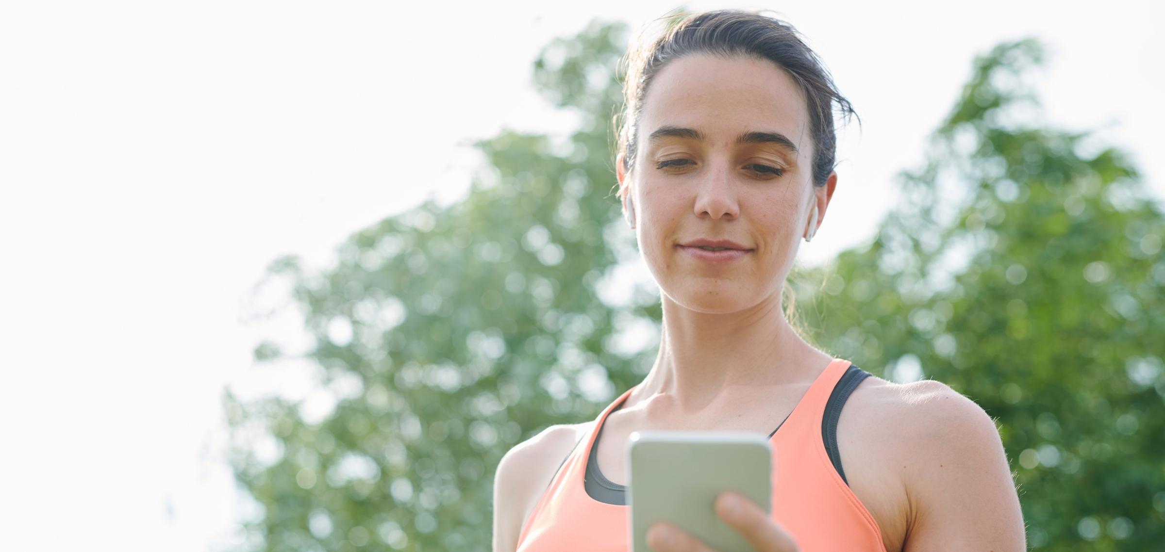 Frau mit ihrem Smartphone setzt Tipps für Yoga Social Media um