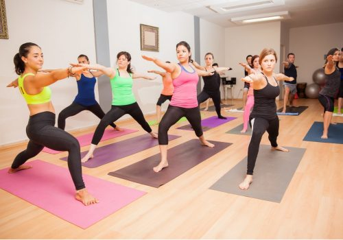 Wide angle view of a female yoga instructor teaching a large class in a gym
