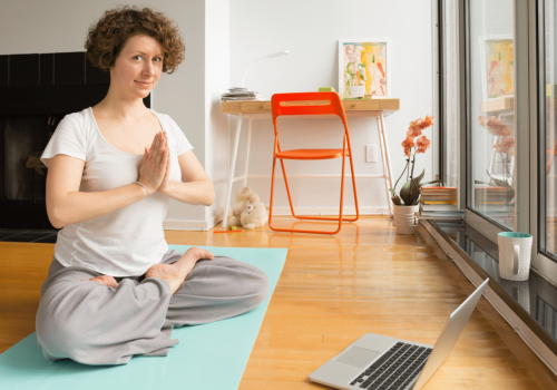Vrouw doet yogapose thuis tijdens online les