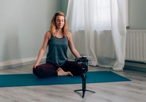 Frau sitzt im Schneidersitz auf ihrer Yogamatte und zeichnet ihre Yoga Stunde mit dem Smartphone auf