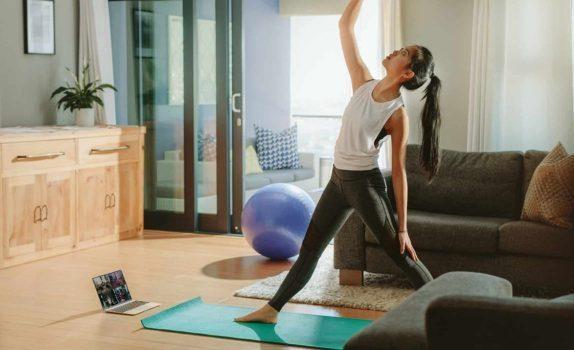 Frau beim Online Yoga zuhause